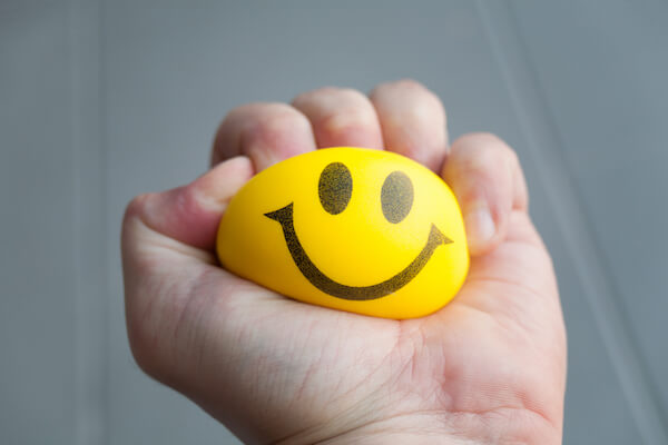 hand squeezing yellow stress ball